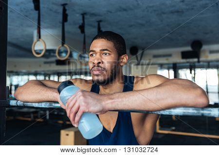 Pensive sports man holding bottle with water and resting in the gym
