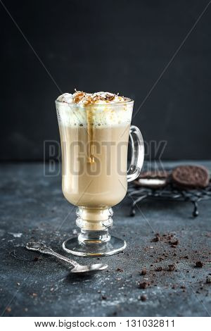 A mug of sweet hot coffee with caramel topping chocolate and milk on grey concrete background. Shallow depth of field.