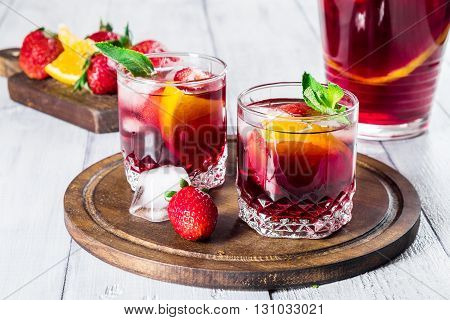 Sangria with fresh strawberries oranges mint and ice on white wooden background. Selective focus.