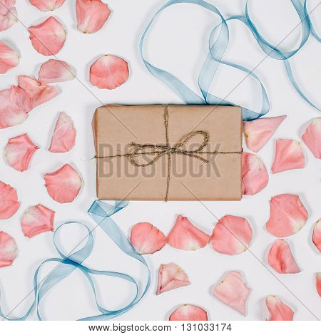 Present in parchment with pink petals and blue ribbon on white background. Top view, flat lay