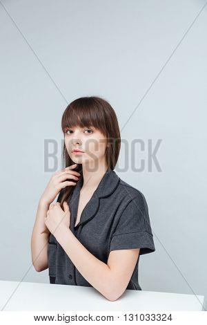 Young woman sitting at the table and looking at camera isolated on a white background