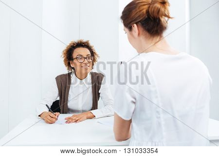Happy african american young businesswoman in glasses interviewing candidate and writing sitting at the table