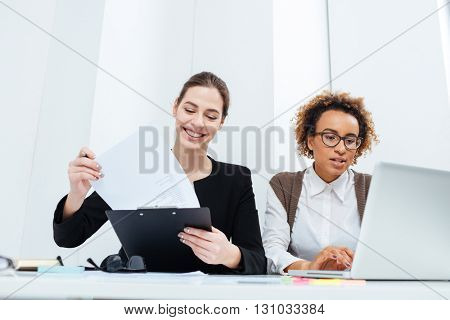 Two happy cute businesswomen using clipboard and laptop and making report together
