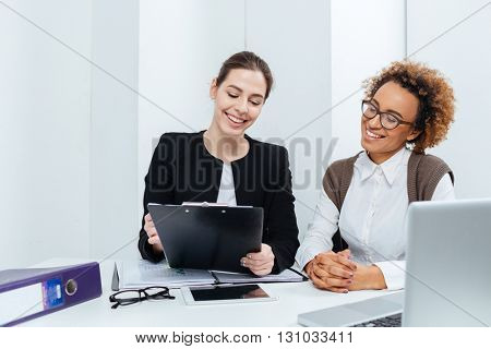 Two cheerful young businesswomen with clipboard working together in office