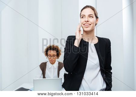 Smiling pretty businesswoman talking on cell phone while her colleague sitting and working with laptop