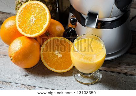 Juicer And Orange Juice In Glass On Wooden Desk