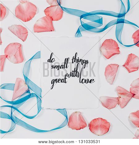 quote do small things with great love written in calligraphy style on paper with pink petals and blue ribbon