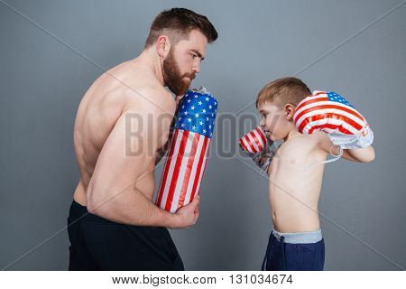 Father and son training using boxing gloves and punching bag over grey background