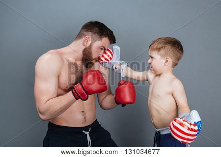 Dad and son playing using boxing gloves together over grey background
