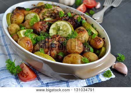 Baked potatoes with chicken and vegetables on a black background