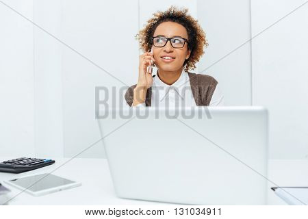 Smiling african american young woman accountant working with laptop and talking on cell phone on workplace