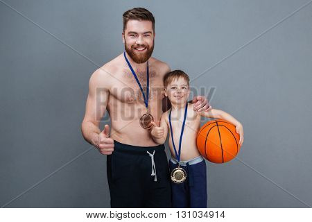 Cheerful man and his son with golden medals and basketball ball showing thumbs up over grey background