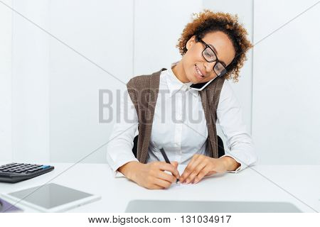Happy african american young woman accountant  talking on cell phone and writing