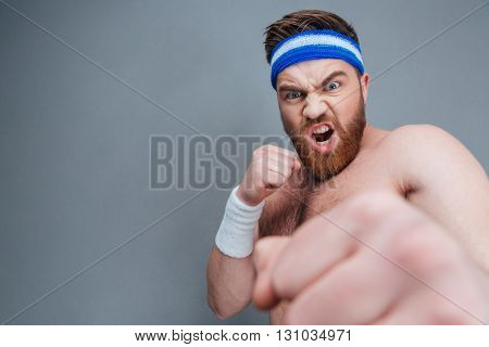Mad irritated young sportsman shouting and punching at camera with his fist over grey background