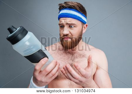 Portrait of sad upset young sportsman with empty bottle for water over grey background