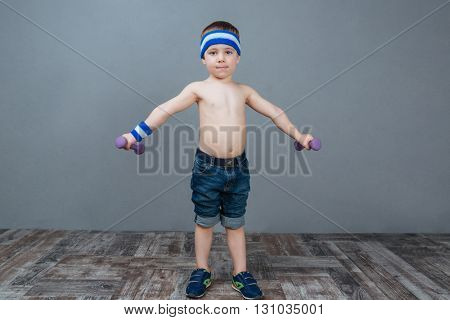 Cute little boy standing and working out using dumbbells over grey background
