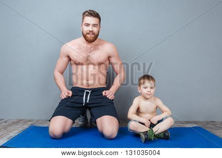 Happy dad and son sitting on blue yoga mat together over grey background