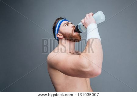Closeup of shirtless bearded young sportsman drinking water from plastic bottle over grey background