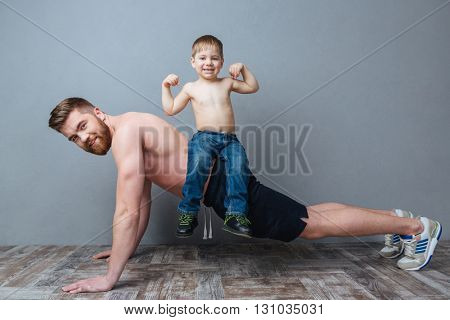 Smiling bearded father doing push-ups with little son sitting on his back over grey background