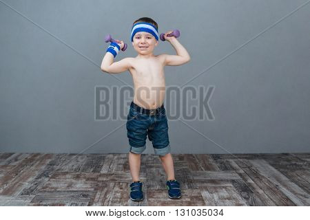 Smiling little boy doing exercises with dumbbells over grey background