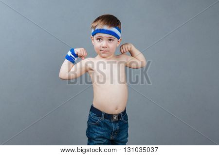 Portrait of shirtless little boy standing and showing biceps over grey background