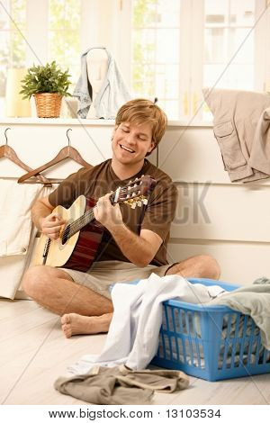 Cheerful guy singing and playing guitar sitting on floor of living room instead of doing housework, washing laundry.