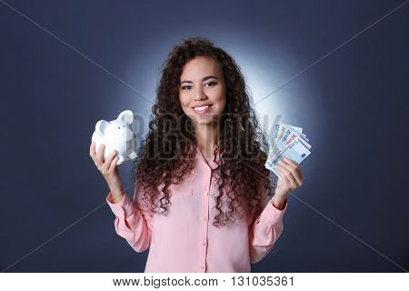 Beautiful young girl holding piggy bank and cash on grey background