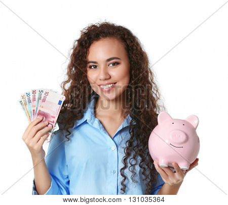 Beautiful young girl holding piggy bank and cash, isolated on white