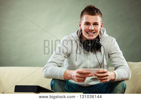 Modern technologies connection leisure concept. Young handsome man relaxing on couch with headphones smartphone and tablet at home