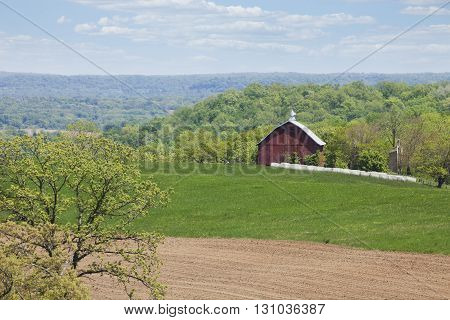An old red barn surrounded by fields and trees in the Iowa countryside on a sunny spring afternoon