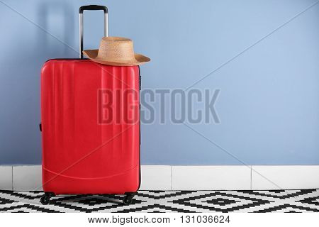Suitcase with hat on blue wall background