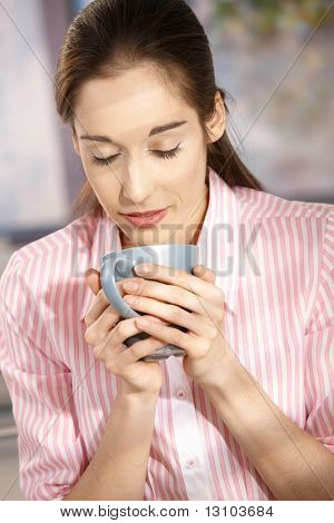 Young woman drinking from mug, smelling coffee with closed eyes.