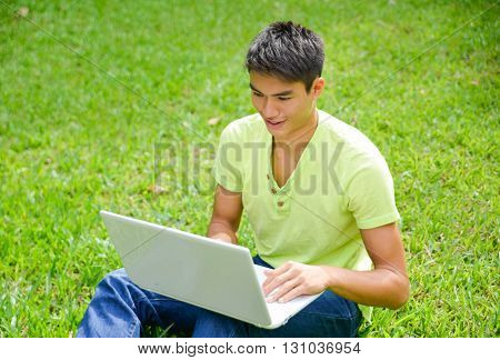 Asian student sitting use laptop at campus grass
