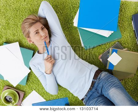 Smiling woman surrounded with documents lying on living room floor, daydreaming with hand under head.
