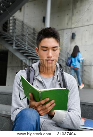 Portrait of college student sitting holding book at a campus