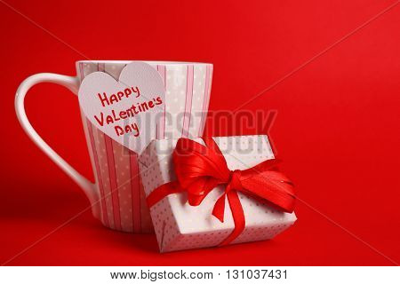 Cup with greeting card and gift box for Valentines Day on red background