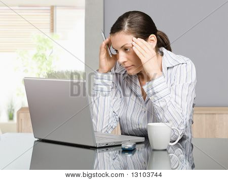 Young woman sitting at desk working with laptop computer at home, serious, thinking.