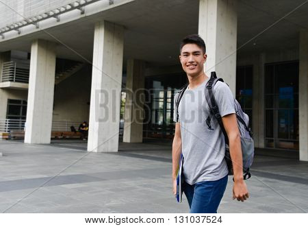 portrait of male standing holding book at campus