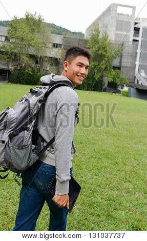Asian student walking with laptop on the green grass, smile