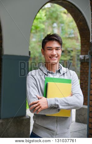 portrait of smile male college student holding book at campus