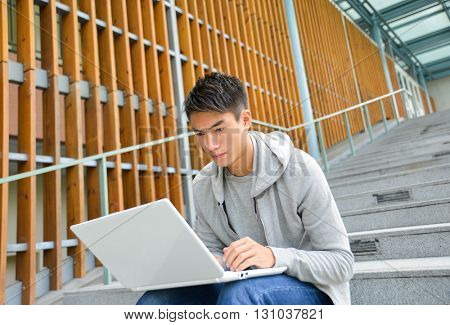 male college student sitting use laptop at campus