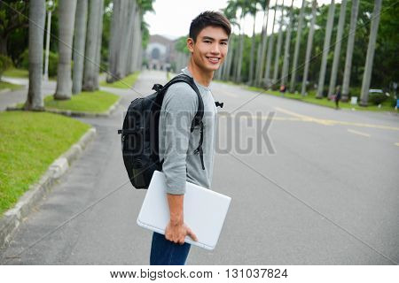 Portrait of college student holding laptop with bag standing at his university