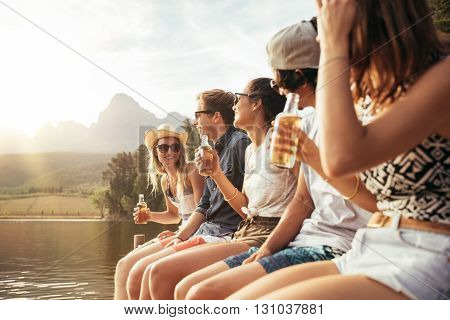 Young Men And Woman Sitting On Jetty With Beers
