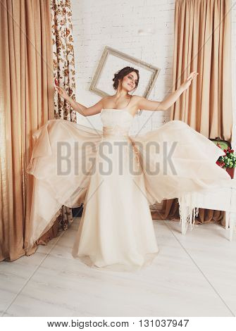 Wedding dress fashion. Beautiful young bride in vintage, shabby chic wedding dress. Rustic wedding dress at model. Girl in champaigne color dress in decorated interior, studio shot, high key