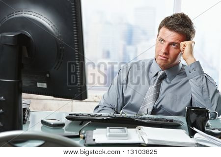Mid-adult businessman making difficult decision looking at screen in office.