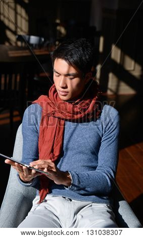 young handsome man using tablet computer in cafe