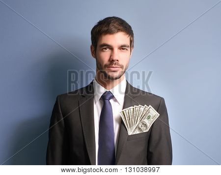 Attractive man in a suit with dollar banknotes in pocket on blue background