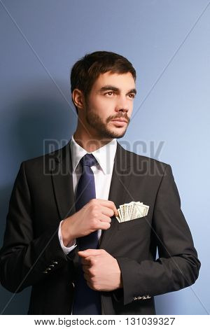 Attractive man getting dollar  banknotes out of suit pocket on grey background
