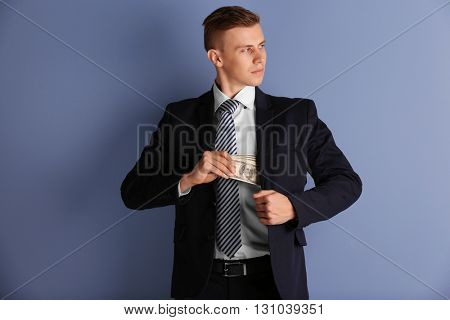 Attractive man hiding dollar banknotes in suit on blue background