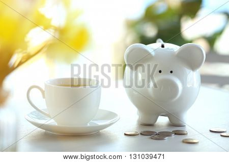 Piggy bank and cup of tea on table